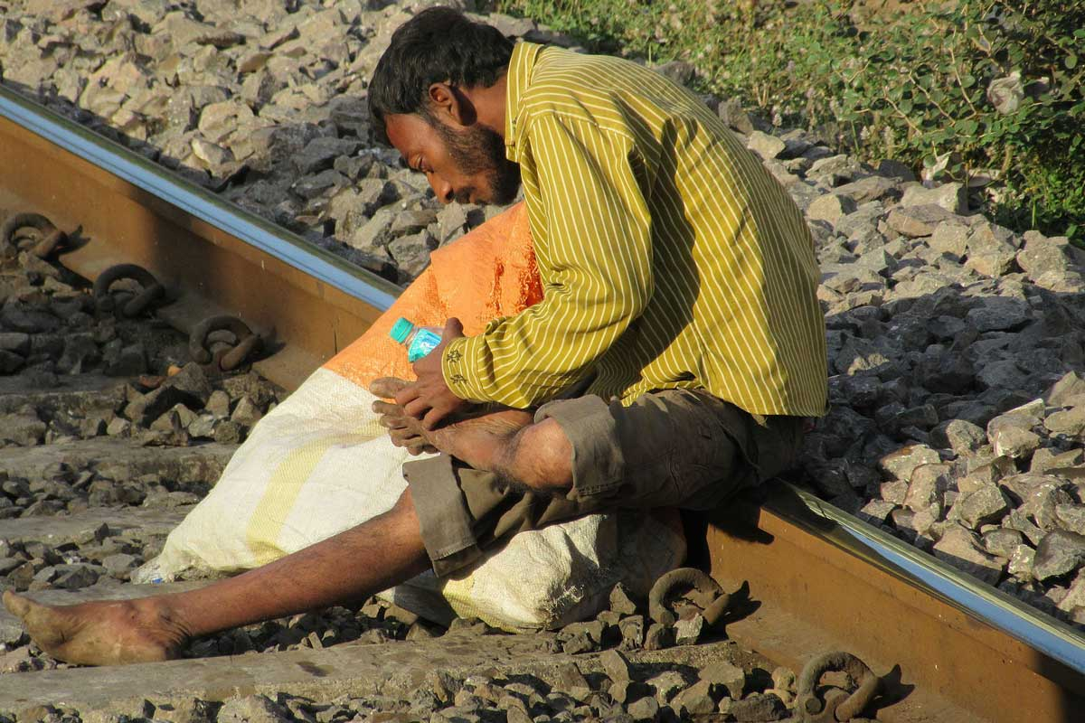 Waste picker cleaning his wounds on the suburban railway track in Mumbai. Image: Hamsa Iyer (CC BY-SA 4.0).
