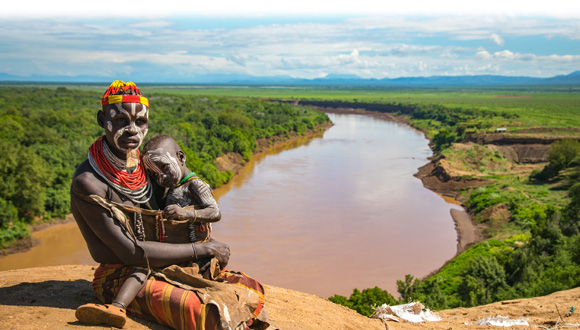 Kara parent and child sitting along the bank of the Omo River. Copyright Kelly Fogel