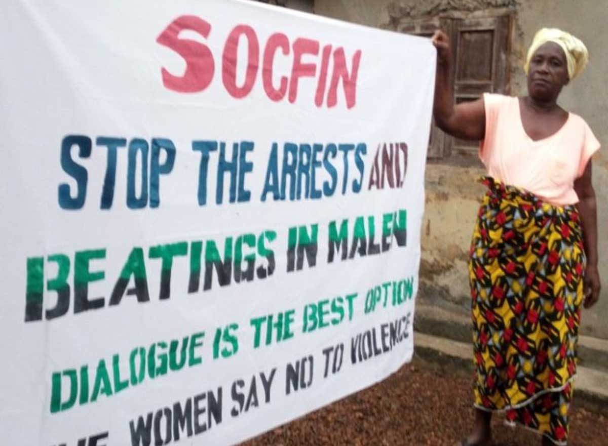 Women with banner: Socfin stop the arrests and beatings in Malen