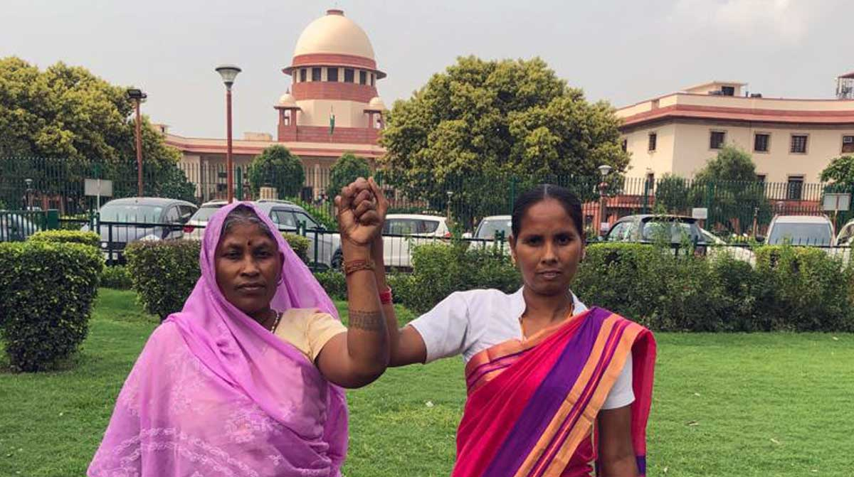 Sokalo Gond of Sonbhadra district and Nivada Rana of Lakhimpur Kheri District stand together outside the Supreme Court of India in Delhi. These two Adivasi women have been an integral part of the legal battle to protect the Forest Rights Act in the Wildlife Trust & Others Vs the Union of India case. Credit: AIUFWP