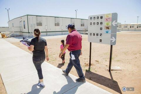 Residents walk past campus map at the STFRC in Dilley, Texas. Credit: Charles Reed, U.S. Immigration and Customs Enforcement