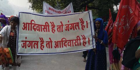 """Women holding banner reading in hindi, """"If there are forests, there will be Adivasis. If there are Adivasis, there will be forests."""" Credit: Oakland Institute"""