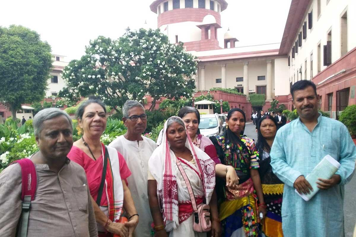 Members of the All India Union of Forest Working People (pictured here) have filed intervention applications to defend the FRA. Here they stand outside the Supreme Court of India after a case hearing on September 12th, when their applications were admitted – formally making them a party to the defense. A negative outcome in this case could lead to the (il)legal dispossession of over 2.5 million people. Credit: The Oakland Institute
