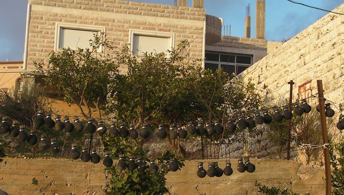 Used IDF gas canisters on garden fences in Nabi Salih. Credit: The Oakland Institute