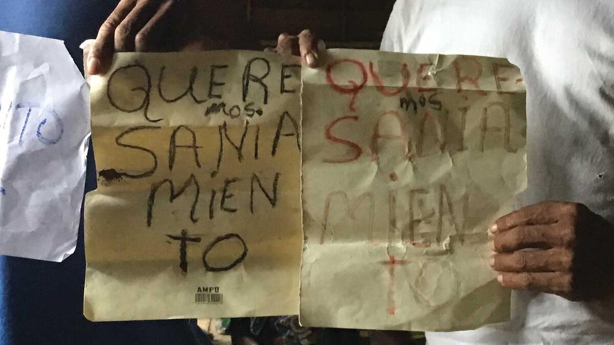 Miskitu villagers holding a sign demanding saneamiento.