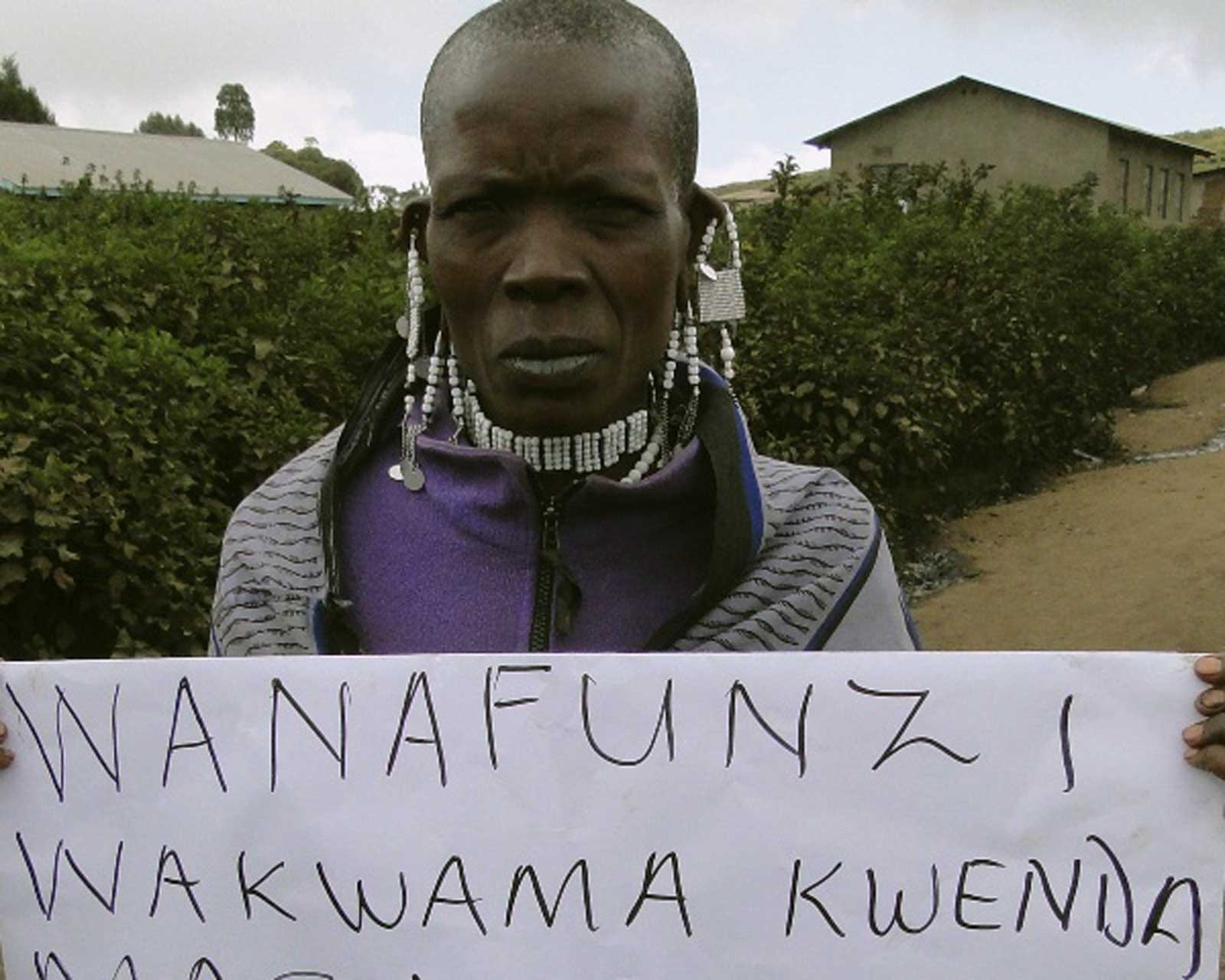 """A Maasai woman holding a sign saying, """"We are unable to pay for education of our children. We do not have any source of income."""""""
