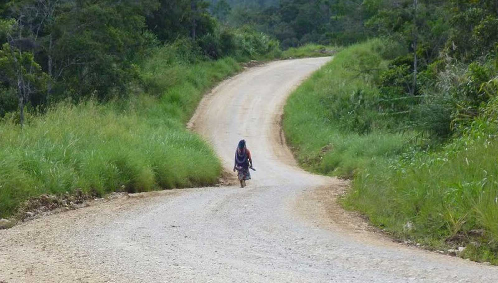 Woman walking on a path into Nogoli, PNG Highlands.